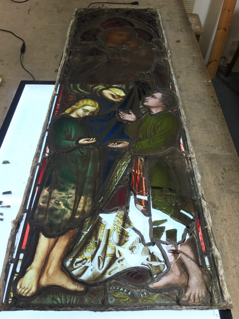 A damed stained glass window being assessed at the studio