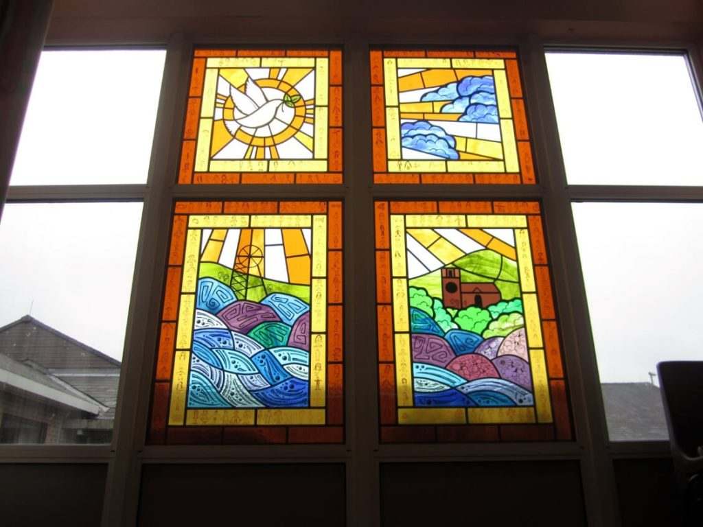 A set of triple glazed stained glass windows that replaced existing clear units for a school in Whitick