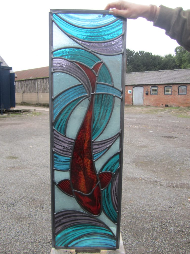 This is one of a pair of handpainted koi carp for either side of a front door.